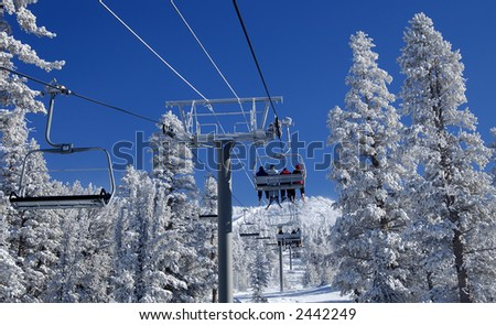Skiers are riding a ski lift on a skiing resort at Lake Tahoe on a cold day after a snowstorm.