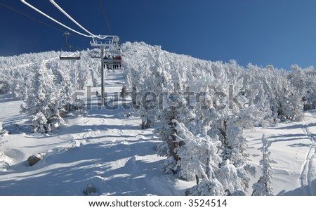 Skiers are riding a ski lift on a skiing resort at Lake Tahoe on a very cold day after a heavy snowstorm. Seats, cables a pillars are covered in frost.