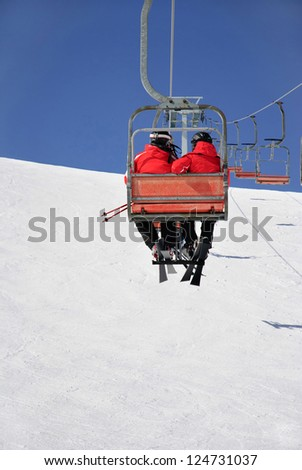 Skiers couple on a ski lift in red skisuit