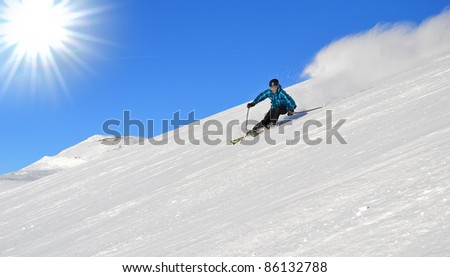 skiers in carving arc on the piste in the Alps in the sun