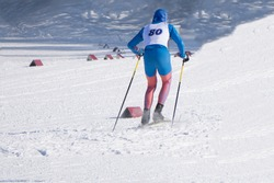 skiers on a ski slope in the resort in the background of a snowy winter in winter, weather permitting