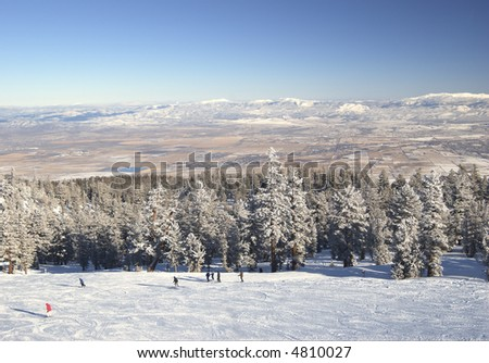 Skiers on the slope above Nevada desert in Lake Tahoe area. Motion blur on one of fast moving skiers.