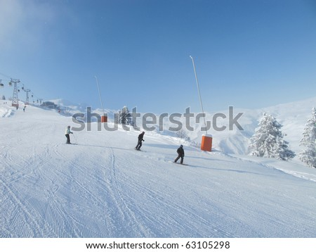 Skiers on wide ski slope on sunny day. Blue sky, Chamonix . French alps.