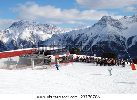 Skiers queuing for a chair-lift in Swiss Alp - stock photo