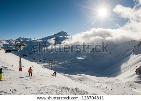 Skiers riding down the mountain to the sunny valley