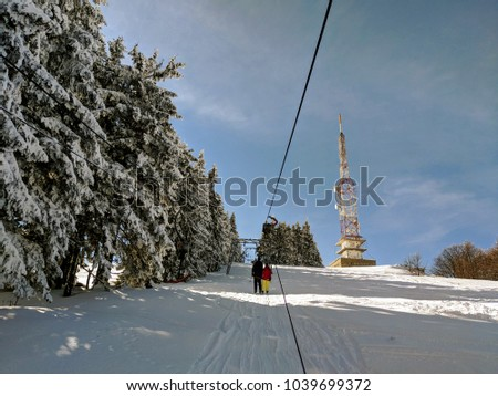 Skiers taking the ski lift to the top. Chair lift/ski lift in a ski resort in the Alps in Austria, Europe. Skiers and snowboarders on the slope. Amazing winter landscape with snowy pine trees #1039699372