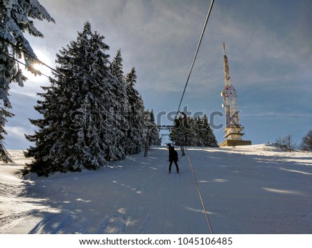 Skiers taking the ski lift to the top. Chair lift/ski lift in a ski resort in the Alps in Austria, Europe. Skiers and snowboarders on the slope. Amazing winter landscape with snowy pine trees #1045106485