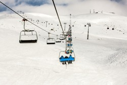 Skiers with backpacks on chair-lift and snowy ski slope at sun winter day. Caucasus Mountains, Georgia, region Gudauri.