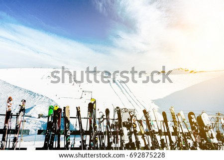 Skies and snowboards in Deux Alps chalet mountain resort with ski slope in background - Panoramic view of french alps - Travel, vacation and winter sport concept - Main focus on gear silhouette #692875228