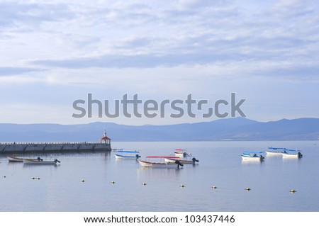 Skiffs and fishing boats anchored in harbor off Lake Chapala pier in Chapala Mexico