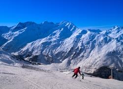 Skiier on slopes on a clear day in St. Anton, Austria - December 2019 - beautiful snowy peaks - winter sports  blue skies