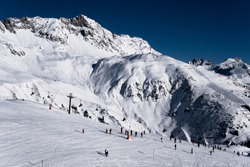 Skiiers on slopes in the beautiful ski resort of St. Anton, Austria - December 2019 - beautiful snowy peaks and winter sports and blue skies in the afternoon
