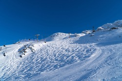 Skiiers on slopes in the ski resort of St. Anton, Austria - December 2019 - beautiful snowy peaks and winter sports with ski lifts