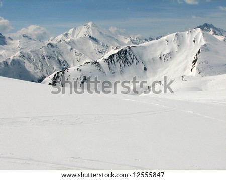 Skiing area in the Alps with high mountains and a chair lift in the back
