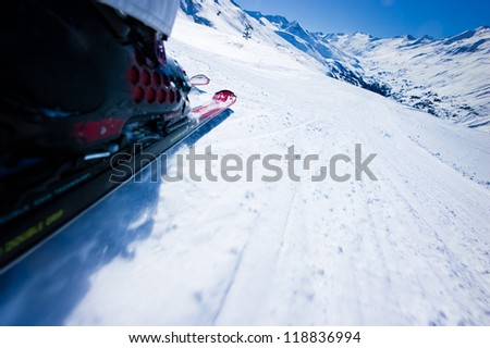 Skiing downhill against the mountains and the blue sky