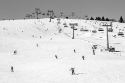 Skiing Hill With People Enjoying Winter Sports Like Skiing And Snowboarding With Chairlift In Scene In Vintage Black And White