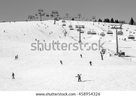 Skiing Hill With People Enjoying Winter Sports Like Skiing And Snowboarding With Chairlift In Scene In Vintage Black And White Zdjęcia stock ©