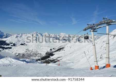 Skiing in the famous ski resort of Verbier in the Swiss Alps. In the background the bernese alps. In the foreground empty slopes with just a few skiers on fresh snow.
