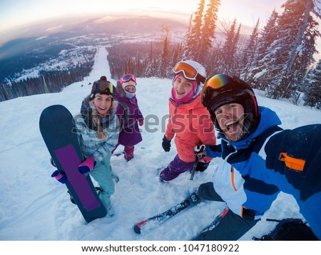 skiing on ski Team of friends makes selfie photo of herself with snowboards and skis. action camera. Sunset. Sheregesh, Kemerovo region, Russia. #1047180922