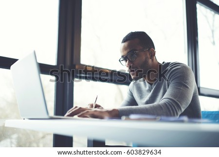 Skilled afro american male IT professional freelancer working on clients project updating software improving code of application working in coffee shop using laptop computer and wireless internet