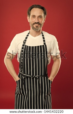Skilled and confident. Senior cook wearing bib apron. Bearded mature man in striped apron. Mature person in cooking apron. Aged master of the household. Doing household. Home cooking. #1441432220
