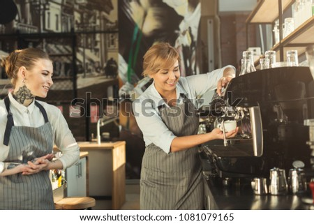 skilled barista teaching young...