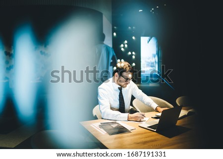 Skilled businessman leadership of enterprise corporation checking status of bank account analyzing report during working process near desktop with modern laptop device, concept of digital management