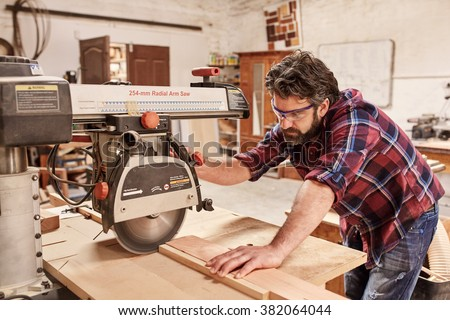 Skilled carpenter in his woodwork workshop, cutting a piece of wood with a radial arm circular saw, and wearing safety goggles