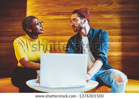 Skilled casually dressed male and female colleagues looking at each other through spectacles talking about work, intelligent multiracial employees discussing project ideas near laptop computer