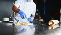 Skilled chef preparing traditional italian pizza  in interior of modern restaurant kitchen with special wood-fired oven. Wearing protective medical face mask and gloves in coronavirus new concept
