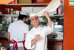 Skilled chef throwing up pizza base dough