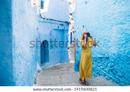 Skilled female journalist walking around ancient city - Morocco taking pictures of architecture Unesco buildings during business trip for exploring berber town, concept of photography hobby