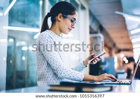 Skilled female receptionist checking notification of mails on cellphone working with laptop computer at desk,professional administrative manager of office using app for organizing data on technologies