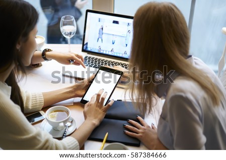 Skilled female trainee IT developers testing application for online shopping providing fast access to web store on digital devices with mock up screen connected to free wireless internet in cafe