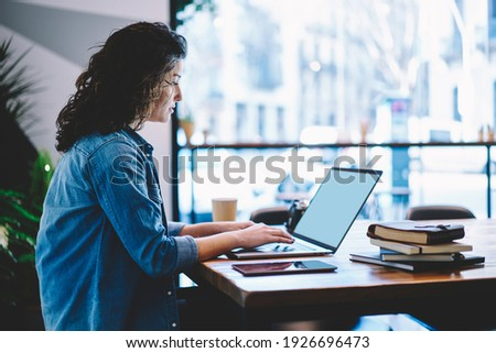 Skilled freelancer checking received information on modern laptop computer with blank screen, Caucasian female student preparing to university exams while e learning on netbook in coworking space Stock photo ©