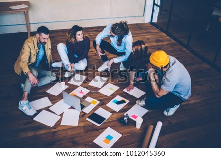 Skilled male and female coworkers sitting on flour communicating about project laying out papers, student having informal meeting with creative coach presenting ideas and brainstorming in office