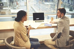 Skilled male formally dressed HR manager of business company having conversation with skilled experienced designer talking about achievements showing projects plannings on laptop with blank screen