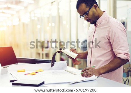 Skilled male restorer reading recommendation from client while making blueprint for building reparation using application on laptop computer connected to wireless internet in office wifi zone