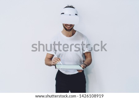 Skilled man typing with digital stylus for interactive touch over tablet for creating augmented 3d dimension standing indoors near promotional background with copy space for cyberspace advertising