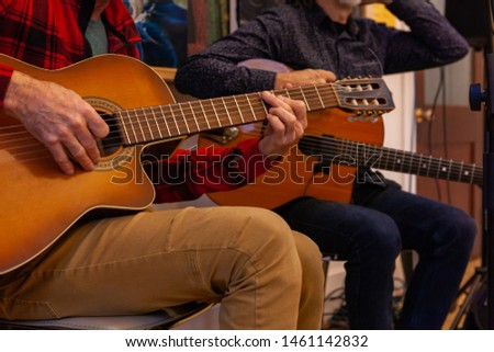 Skilled musicians play rhythm sounds. A close up view on the hands of two guitarists as they perform a music piece sitting down indoors, men playing string instruments with copy space on the right. #1461142832