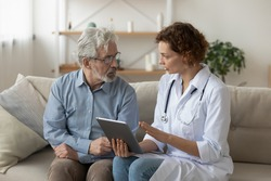Skilled professional physician doctor prescribing illness treatment, showing health test results on digital computer tablet to concentrated older retired patient at home, sitting together on sofa.
