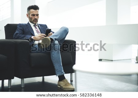Skilled successful male owner of trading corporation reading notification of working day schedule on smartphone connected to wireless internet while sitting in office preparing for conference meeting #582336148