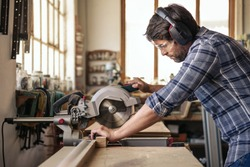 Skilled woodworker wearing safety gear using a mitre saw to cut a piece of wood while working alone in his woodworking studio