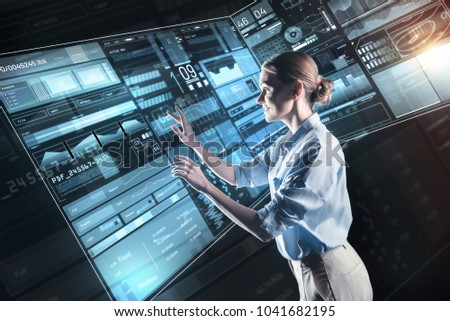 Skilled worker. Cheerful kind attentive programmer feeling good while being at work and touching the transparent screen of a wonderful futuristic device #1041682195