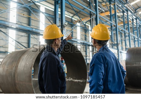 Skilled worker pointing up while giving instructions to an apprentice in a factory manufacturing boilers