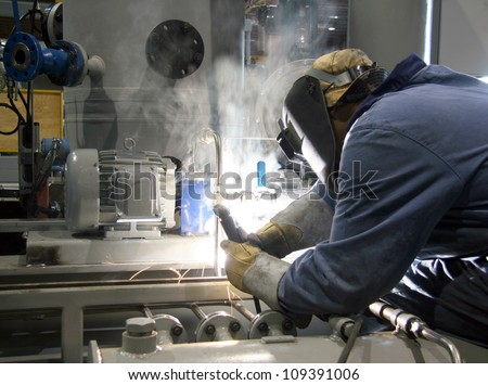 Skilled working factory welder - stock photo