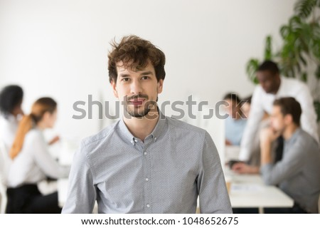 Skilled young professional looking at camera posing in office with team colleagues at background, successful startup founder, corporate employee or sales manager, business leader head shot portrait