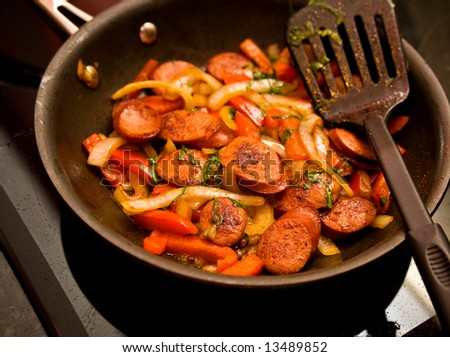 Skillet of sausage and red bell peppers on the stove