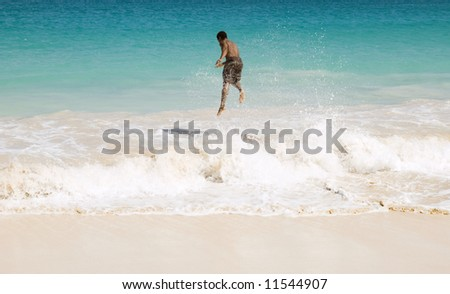 Skimboarder jumping wave.