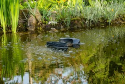 Skimmer Messner floats on surface of water in garden pond against blurred background of stone banks. Selective focus. Skimmer removes debris and dirt and saturates water with air.